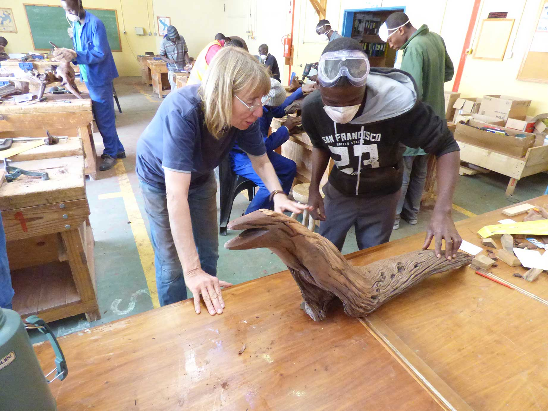 Christiane Stolhofer is discussing Kurika Diakuwa' s sculpture in the 2016 Wood Sculpture Workshop in Maun, Botswana. Both of them are leaning over a long brown reptile looking sculpture, being in deep conversation.