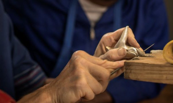 A close up photo of the artists hands filing a silver miniature.