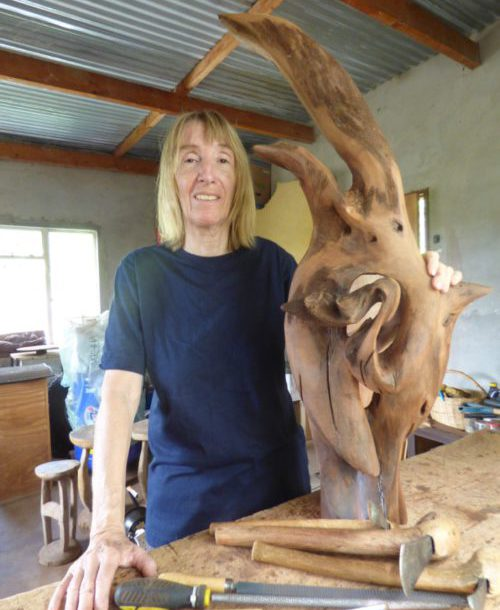 The artist Christiane Stolhofer is standing at her work bench holding her wooden sculpture. On the bench are lying two wood working adzes.
