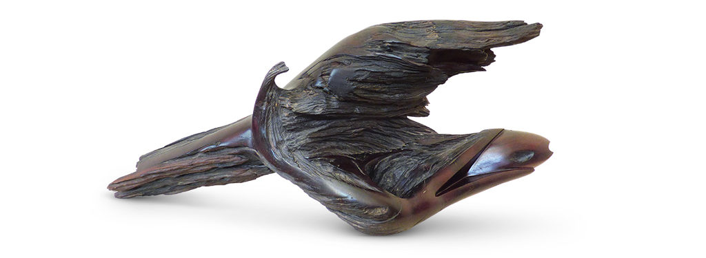 Wood Sculpture titled Gotcha! in dark Mopane wood. A bird is catching a fish, not strictly figurative. The wings of the bird, the open beak and the fish are all emerging out of the waves of the water.