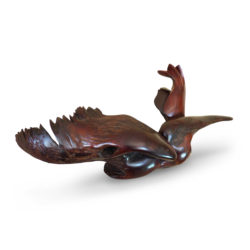Swamp Seraph, the wood sculpture shows a powerful seated bird with large wings and a long beak from the side angle.