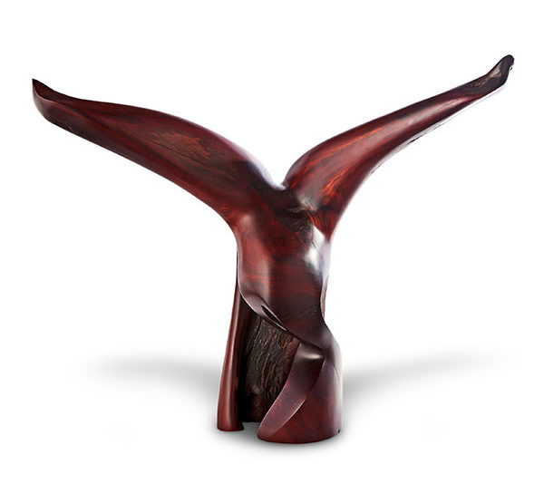 Wood sculpture Catch of the Day, resembling a bird of prey, raising its wings. The wood is dark brown. with a fine finished surface. View is from the front.
