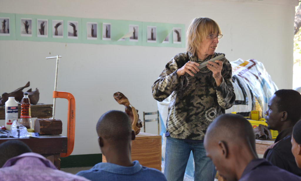 Facilitator Christiane Stolhofer is holding a sharpening stone whilst teaching during the sculpture workshop at Nhabe Museum in Maun in June 2015