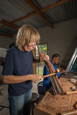 Christiane carving a piece of wood using a petlwanamor hand made adze