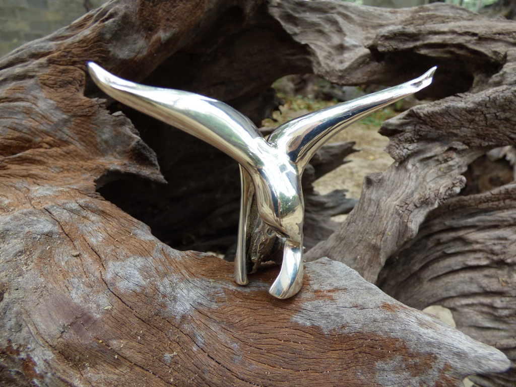 Front view of miniature silver sculpture titled Catch of the Day, against a background of weathered wood.
