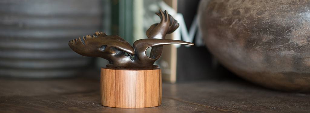 Miniature in brown bronze titled Swamp Seraph, a bird with raised wings on a olive wood base.