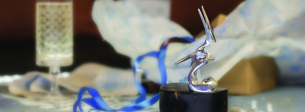 Miniature titled Reed Singer, a singing bird is displayed on an ebony base, in the background is a gift box, blue ribbon and a filled champagne glass.