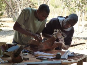 Two Botswana artists working together on sanding a wood sculpture shaped like a bird