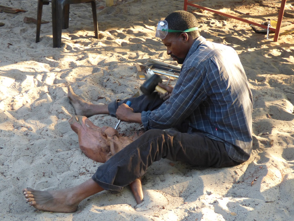 Artist Malaki Sembumburu, seated on the ground, shaping his elephant sculpture