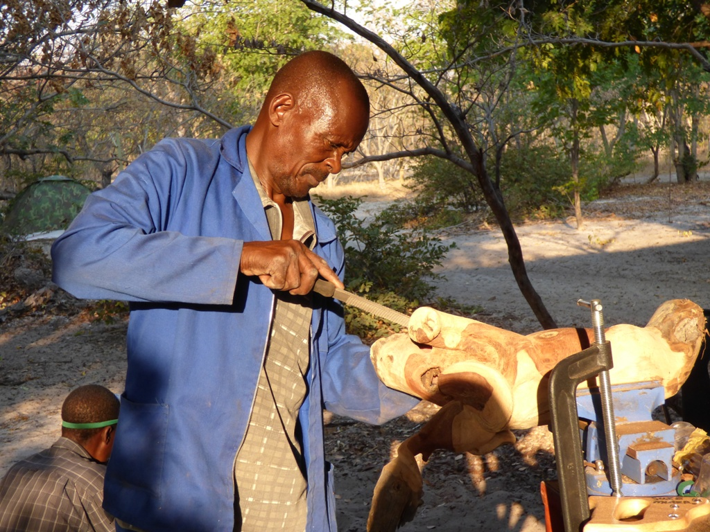 Artist Suze Mutero rasping his elephant wood carving